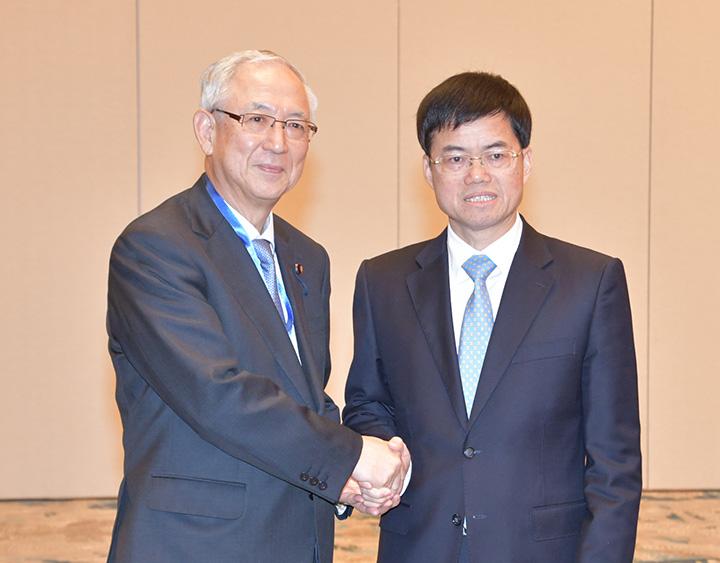 市党委書記(右)と握手する井上幹事長=24日 アモイ市