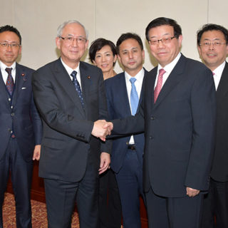 李主任(右から2人目)と握手する井上幹事長(左隣)ら公明党のメンバー=27日 北京市