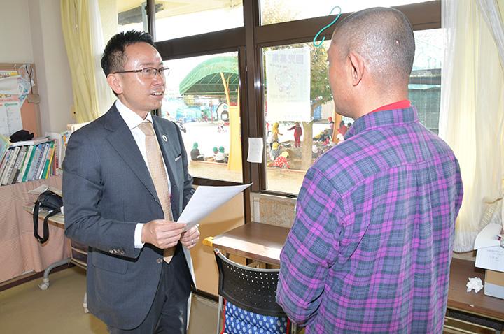 幼稚園の園長(右)から話を聞く伊藤県代表=25日 名古屋市